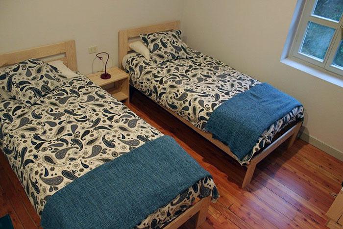 cama individual y estanterías lufe en el hostal arrigorri ostatua