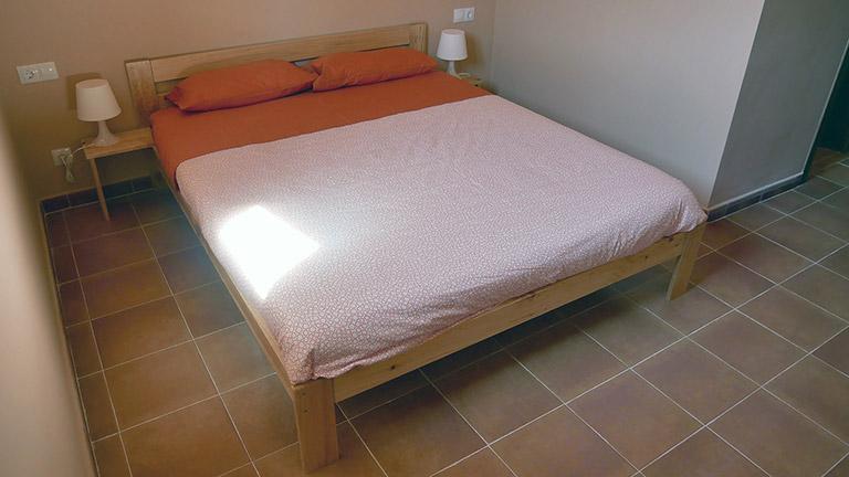 Las cama de matrimonio con mesilla de pata del Hogar LUFE, el Albergue Los Griegos en Teruel.